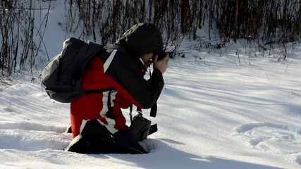 man with a camera in the snow