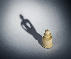 A chess pawn casting a king piece shadow