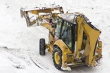 An excavator cleans snow blocked parking