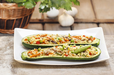 Zucchini stuffed with couscous vegetable salad on wooden table