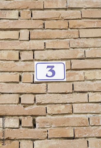 Number three on a brick wall