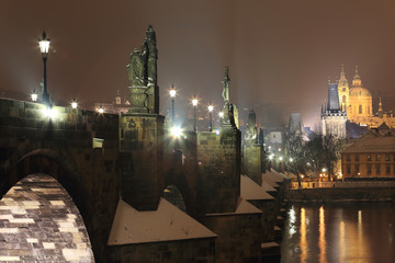 Night snowy Prague St. Nicholas' Cathedral with Charles Bridge