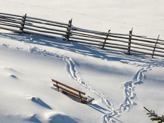 Ruhebank und Holzzaun im Schnee