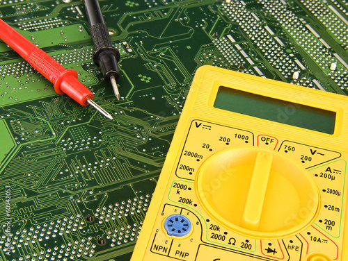 Yellow multimeter on green motherboard pcb