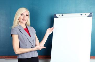 School teacher near whiteboard on blackboard background