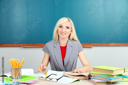 School teacher sitting at table on blackboard background