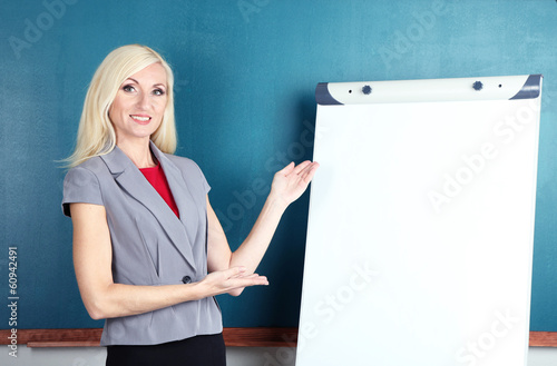 School teacher near whiteboard on blackboard background