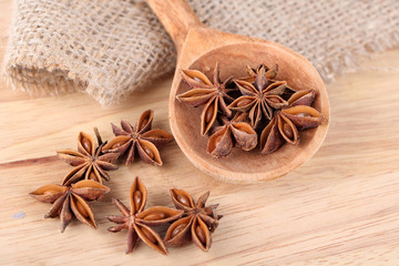 Star anise in wooden spoon, on wooden background