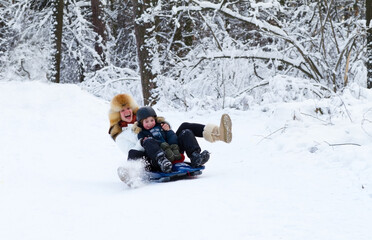 Mother and son enjoying a sleigh ride on a beautiful winter day