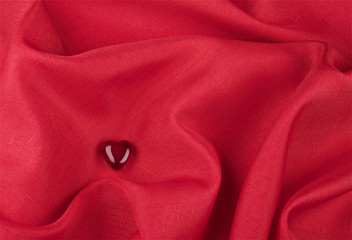 One heart of glass on the red fabric background