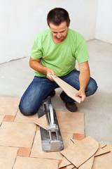 Worker cutting ceramic floor tiles
