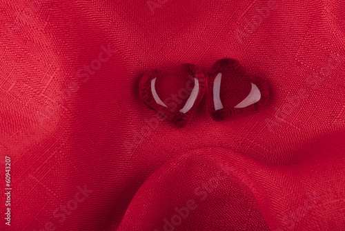 Two hearts of glass on the red fabric background