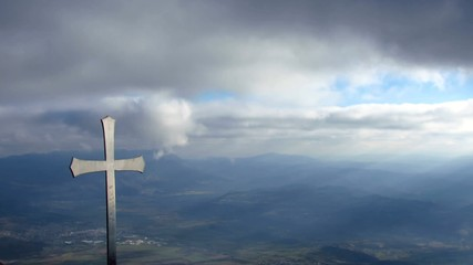 Cross on the top of a mountain with sun rays - pan right