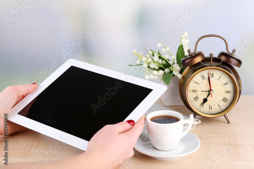 Tablet, cup of coffee and alarm clock, close up