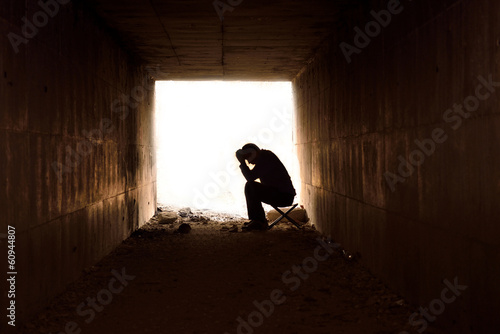 depressed man sitting in the tunnel