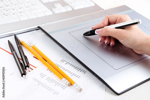 Female hand using graphics tablet on table close up