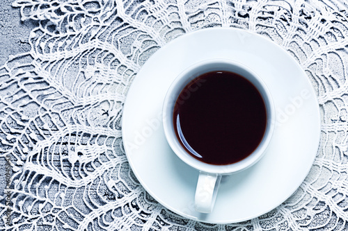 close up of coffee cup on table with crochet doily