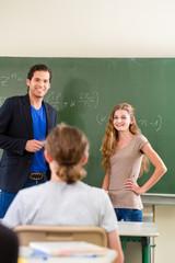 Lehrer prüft Schüler  im Mathe Unterricht in Schule