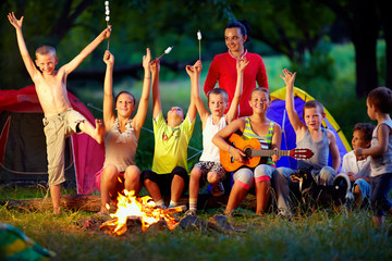 laughing kids friends having fun around campfire