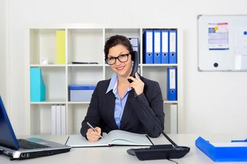 Junge Frau im Büro berät am Telefon
