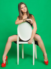 beautiful girl in a black dress, sitting on a chair