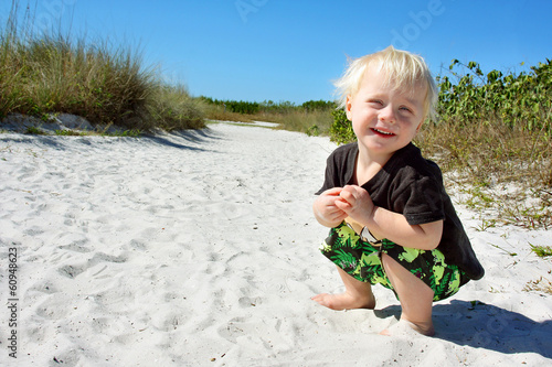 Smiling Young Child Playing in Sand at Beach