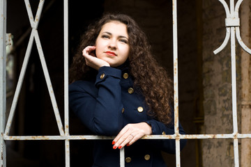 Portrait of a beautiful young brunette in a blue coat