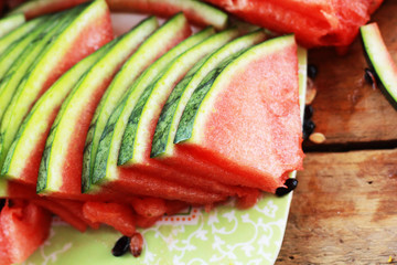 Watermelon fruit sliced into pieces on the wooden floor.