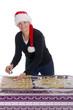 Frau mit Weihnachtsmannmütze backt Plätzchen