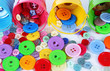Colorful buttons strewn from buckets close-up