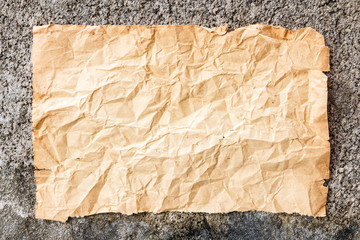 old crumpled paper on cement wall