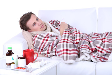 Guy wrapped in plaid lies on sofa is ill