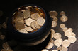 Golden coins in ceramic pot, on wooden table on dark background