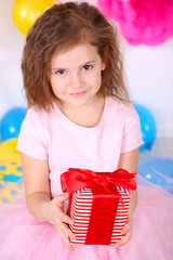 Pretty little girl with gift celebrate her birthday