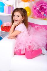 Pretty little girl sitting on sofa on celebratory background