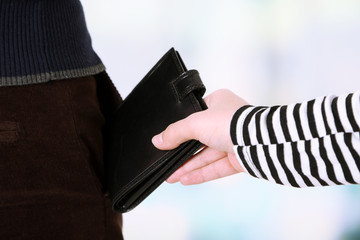 Pickpocket are stealing wallet from pocket, close up,