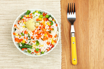 Cooked rice with vegetables on wooden table