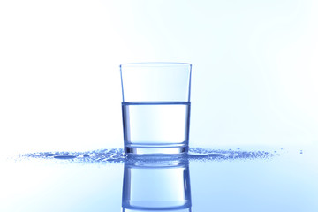 Water in  glass, on blue background