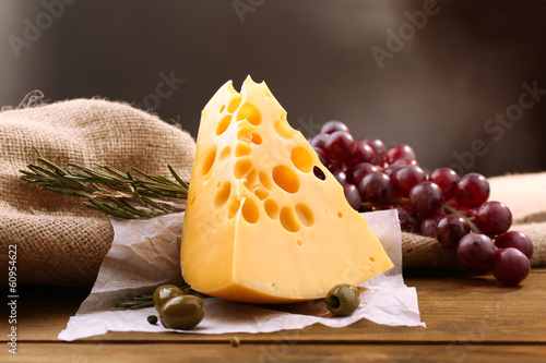 Piece of cheese on plate with green olives, on wooden