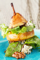Original way to serve pear salad with green leafs, blue cheese a