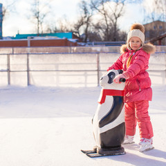 Little cheerful girl learning to skate on the rink