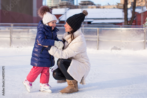 Smiling young mother and her cute little daughter ice skating
