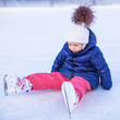 Little adorable girl sitting on the ice with skates after the