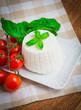 Ricotta with basil and cherry tomatoes on wooden table
