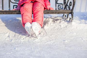 Little skater's legs standing on winter ice rink