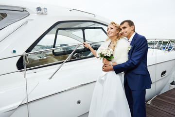 Romantic bride and groom on the pier with yacht