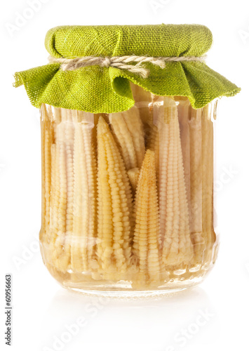 Preserved mini corn ears in glass jar isolated on white backgrou