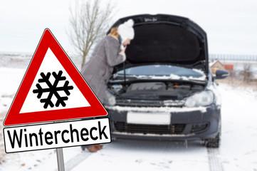 Schild Wintercheck und Frau mit kaputtem Auto