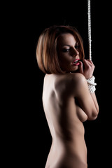 Beautiful naked woman posing with hands bound