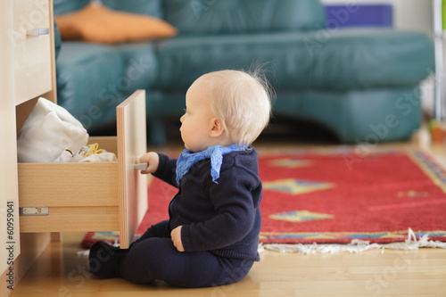 Little boy trying to open and look inside drawer chest.